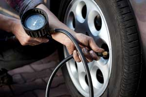 Man checking tyre pressure image